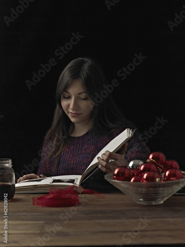 A woman sitting at a table reading a book. A glass bowl of red shiny baubles, and a coil of red ribbon.