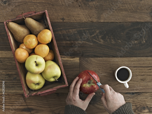 A wooden table top with variety of wood colour and grain. A box of fresh fruits, pears and oranges. A person using a knife to chop an apple.