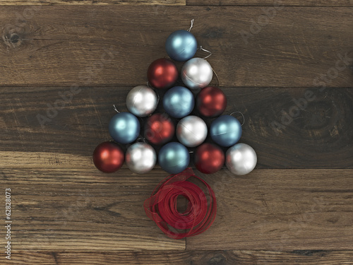 A collection of blue, red and silver ornaments arranged in a triangular shape on a wooden board. A Christmas tree shape with a red ribbon coiled at the base.