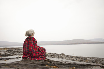 A woman looking out over the water on the shores of a calm lake, wrapped in a tartan rug.