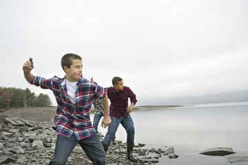 A day out at Ashokan lake. Three boys on the shore throwing skimmers pebbles across the water.
