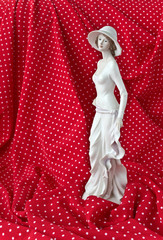 Statuette of a woman in a white dress on a red background