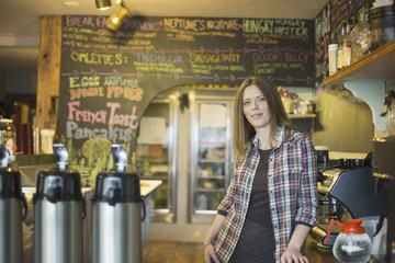 A coffee shop and cafe in High Falls called The Last Bite. A woman leaning on the counter, by the coffee machine.