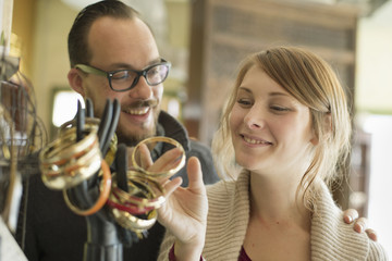 Two people, a man and woman looking at the objects displayed on a mannequin hand, antique jewellery and objects.