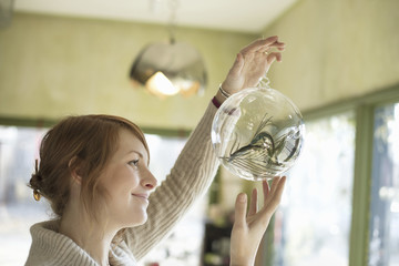 A woman holding up a large glass sphere, clear glass with a decorative objects inside.