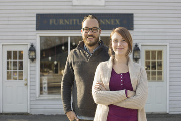 A man and woman standing outside a storefront on a street. A couple running an antique shop.