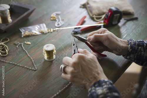 A tabletop with jewellery making equipment. Hands twisting wire on a necklace.