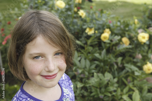 A child in a garden looking up and smiling.