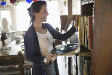 A woman in an antique store in a small town, with objects and furniture from the past. Looking at blackk vinyl records.