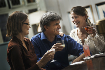 Three people meeting for a drink.  Two women and a man sitting at a bar. Friends socialising.