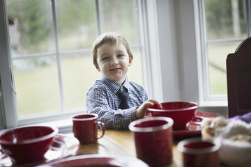 A child sitting at a table in a family home. A table laid for a meal.