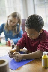 Children in a family home.  Two children sitting at the table, using paint and paper to create decorations.