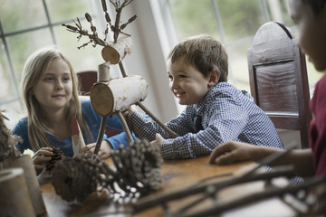 Three children sitting at a table in family home. A twig reindeer in the centre, with branches and twigs to make objects.