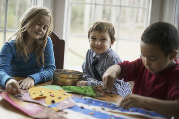 Children in a family home.  Three children creating pictures, with glue and stickers. Craftwork.