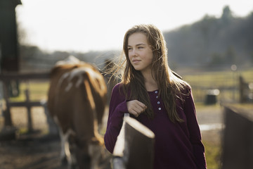 A girl leaning on a paddock fence, and a grazing horse in the background, on an organic farm.