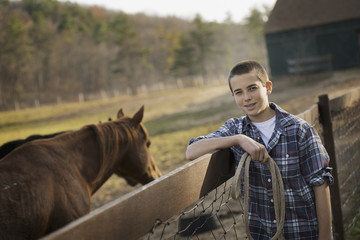 A boy standing by the fence of a horse paddock. A bay horse.