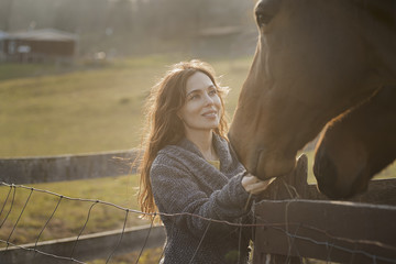 A woman stroking the muzzles of two horses in a paddock on an organic farm.