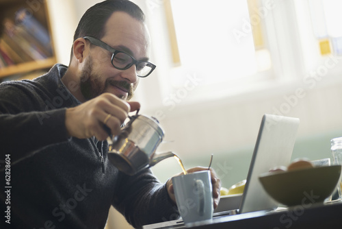 A bearded man having a drink of coffee. An open laptop computer on the counter.