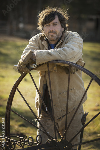Working on an organic farm. A man in overalls wearing work gloves, leaning on a round metal wheel with spokes.