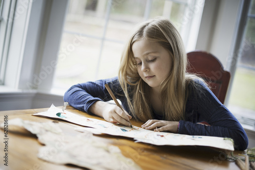 A family home. A young girl sitting at a table drawing on a large piece of paper. Holding a pencil.