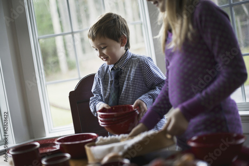 A family home. Two children laying the table with crockery for a meal.