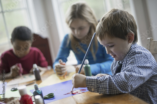 Children in a family home.  Three children sitting at a table using glue and paint to create decorations.