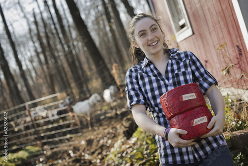 A young woman standing outside a dairy farm building holding two blocks of cheese.