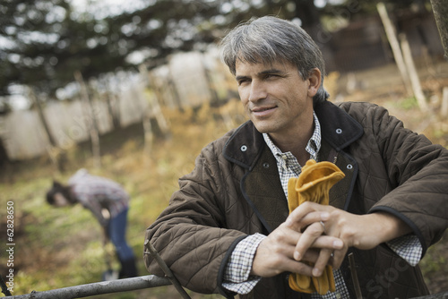 A man in a brown jacket, holding leather work gloves on an organic farm. A person digging in the ground with a spade.