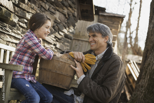 A man and a child on an organic farm. A young girl sitting on a fence, with a wooden pail. Man holding work gloves.