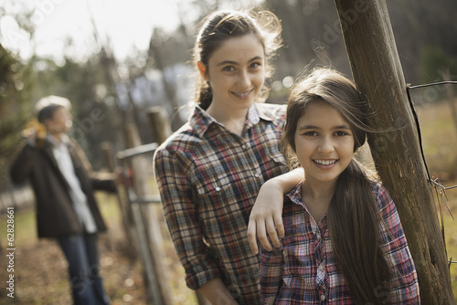 Two young girls beside a paddock fence, and a man in the background. An organic farm.