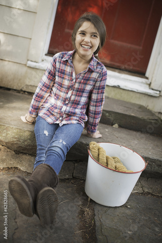 A girl sitting on a step, with a large iron pail and gloves.