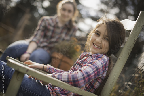 Two children sitting outdoors in a garden on an organic farm.