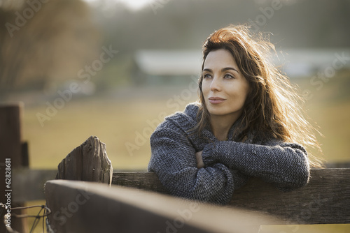 A woman leaning on a fence on an organic farm.