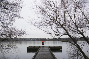 A woman standing at the end of a dock with an orange umbrella on a cloudy, grey day in Seattle.