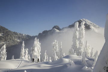 Two hikers enjoy a blue bird day in the middle of winter in the snow covered Cascade Mountains.
