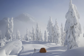 A bright orange tent sits on a snowy ridge overlooking a mountain in the distance.
