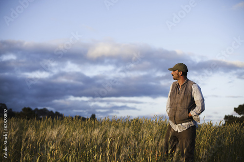 A man standing looking over the crops and fields at the Homeless Garden Project in Santa Cruz, at sunset.