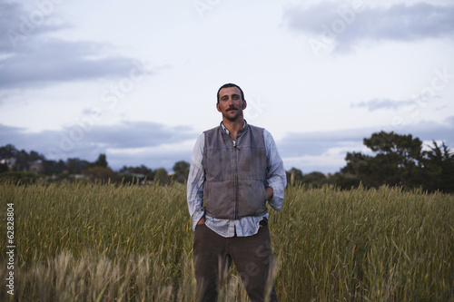 A man standing by a field of growing cereal crop, at the social care and work project, the Homeless Garden Project in Santa Cruz.