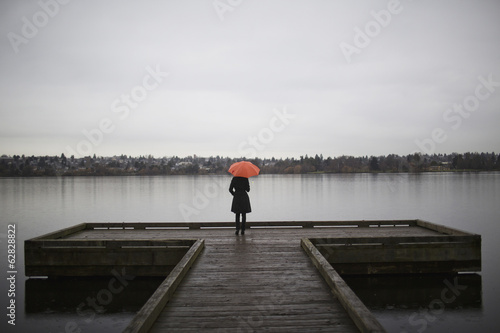 A woman wearing all black and holding an orange umbrella stands on the edge of a dock on a grey and cloudy day in Seattle, WA