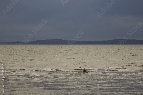 A kayaker paddles his sea kayak in the Puget Sound on a dark and cloudy evening.