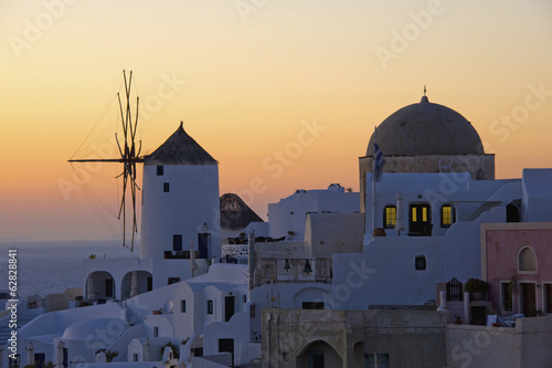 The historic white washed houses, windmills and domed church of Oia town on Santorini island