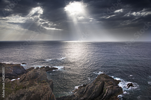 Cabo Sardao coastline in Portugal. Sun streaming through cloud on to the sea.