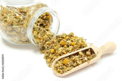 Dried chamomile in glass jar and on wooden spoon