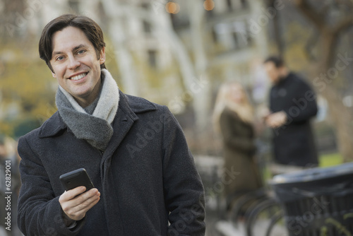 Man in urban park with smartphone