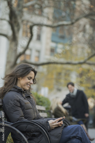 Woman seated in urban park with smartphone
