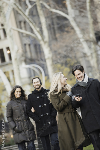Couple walking in urban park with smartphone
