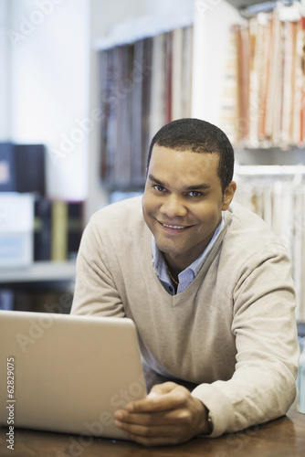 Man working in design shop with laptop