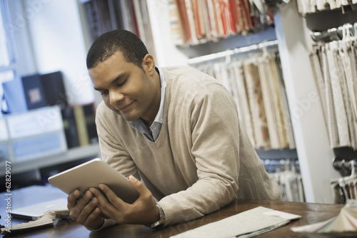 Man working in design shop with tablet