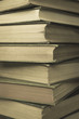 A stack of old hard cover books, with worn edges and aged yellowing paper.