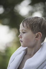 A young boy with wet hair, wrapped in a towel after swimming.